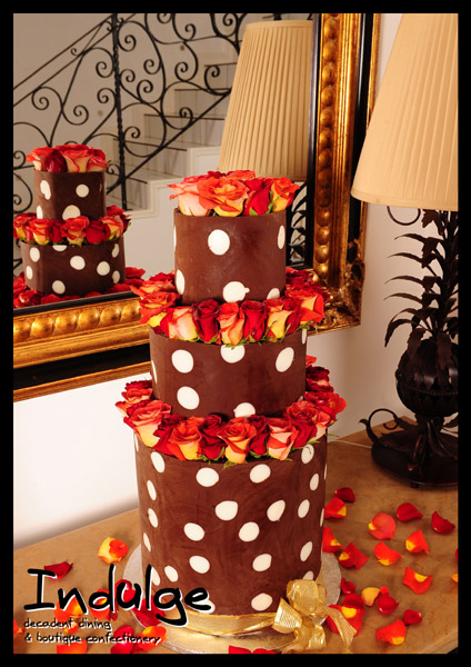 milk chocolate 3 tiered wedding cake with white chocolate polka dots and decorated with roses
